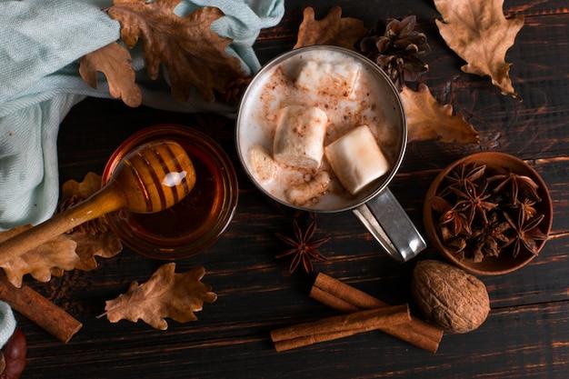 Mug en fer avec cacao, miel, guimauve, épices, sur fond de foulard, feuilles sèches sur une table en bois. ambiance d'automne, une boisson réchauffante. fond