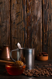 Mug en fer avec café noir, miel et grains de café sur une table en bois. fond