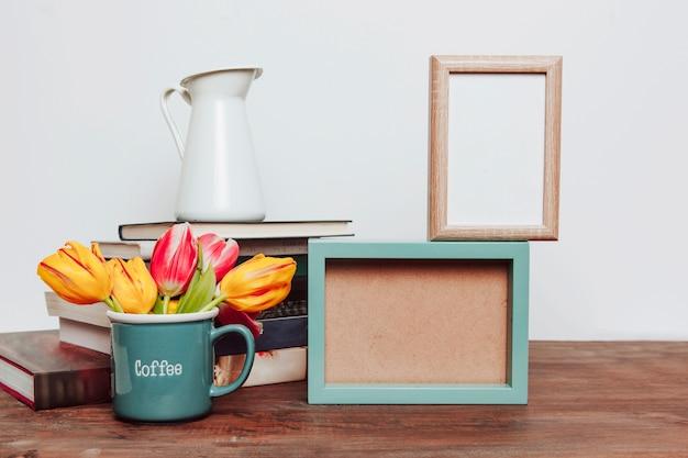 Mug avec des fleurs près des cadres et des livres