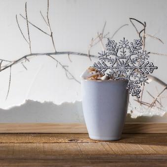 Mug avec flocon de neige jouet sur table en bois près de la rive de la neige