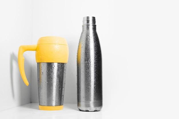 Mug isotherme en acier jaune et bouteille thermique en acier inoxydable éco pulvérisée d'eau sur blanc.