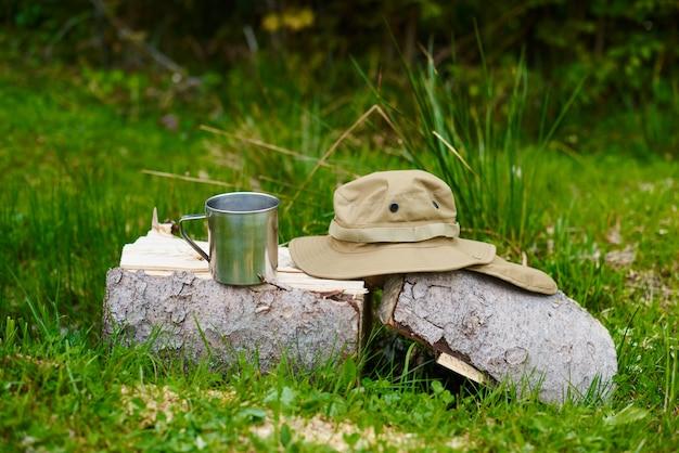 Mug en métal et chapeau de touriste avec des champs se trouvent sur un rondin