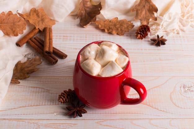 Mug rouge avec cacao et guimauves, sur fond de foulard et feuilles sèches. ambiance d'automne, une boisson réchauffante.