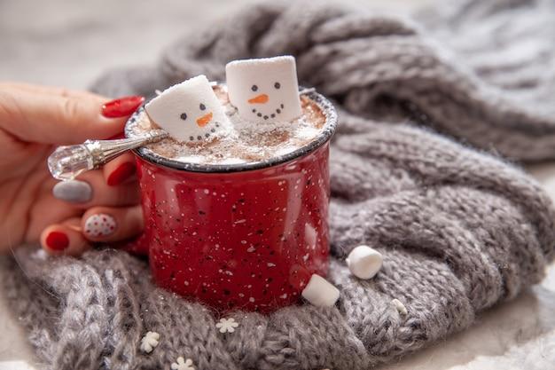 Mug rouge avec chocolat chaud avec bonhomme de guimauve fondu dans les mains d'une femme