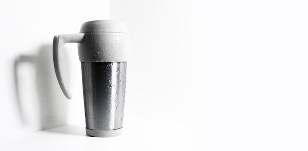 Mug thermo pulvérisé avec de l'eau sur blanc