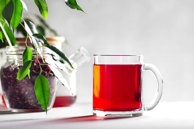 Mug transparent avec thé rouge sur fond gris, à côté d'un pot avec de l'hibiscus et une théière