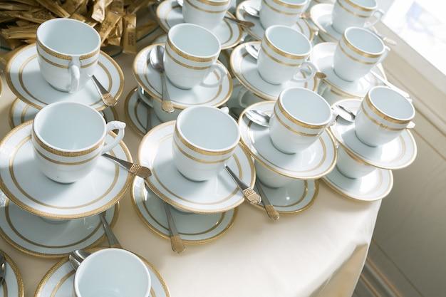 Mugs blancs et dorés, tasses à thé ou à café avec soucoupes, debout les uns sur les autres