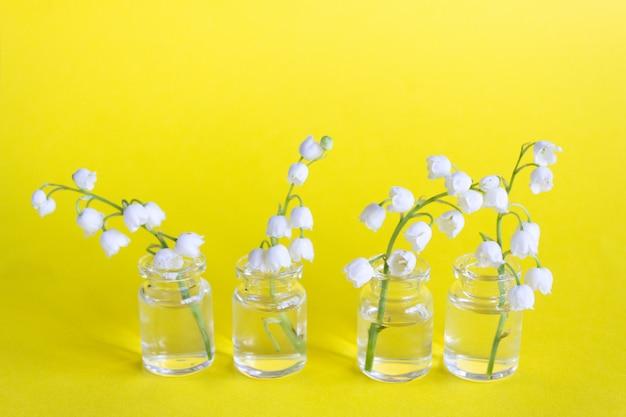Le muguet fleurit dans des bocaux en verre sur un fond jaune