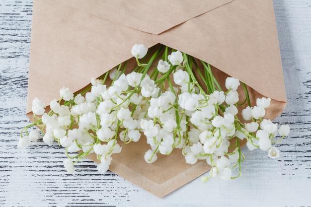 Muguet sur mur en bois blanc. vue de dessus du muguet dans une enveloppe artisanale.