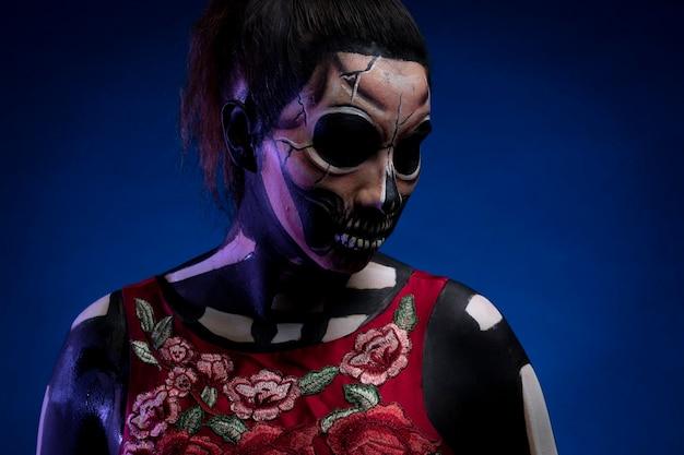 Mujer con body paint de calavera con vestido rojo y fondo azul por dia de muertos