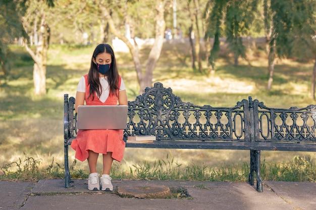 Mujer Con Mascarilla Trabajando En Linea Desde Un Parque Sentada En Una Banca Photo Premium