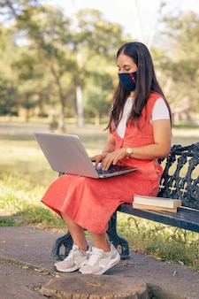 Mujer con mascarilla trabajando en linea desde un parque sentada en una banca