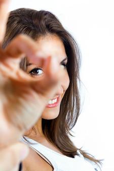 Mujer joven faisant el signo ok sur fondo blanco