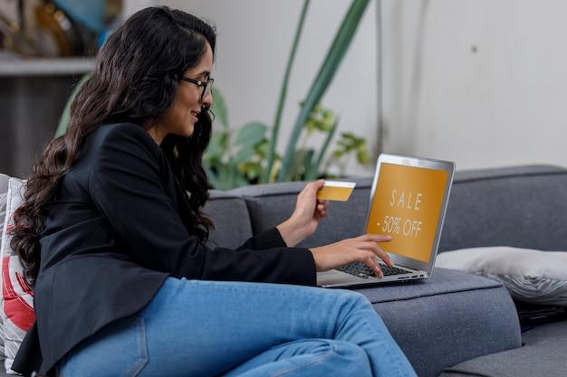 Mujer latina comprando en line desde su casa en su laptop y pagando con su tarjeta de credito