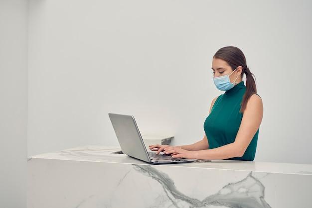 Mujer latina con cubrebocas trabajando en su laptop en la recepcion