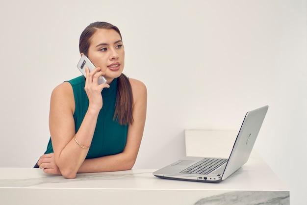 Mujer Latina Hablando Por Telefono Mientras Trabaja En Su Laptop Photo Premium