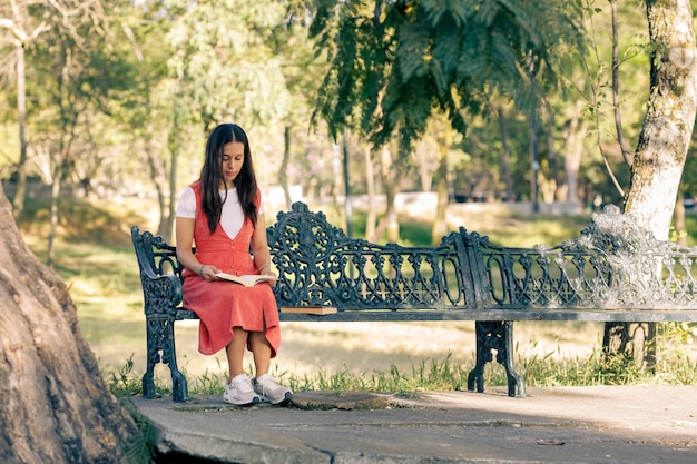 Mujer Latina Sentada En Una Banca De Un Parque Leyendo Un Libro Photo Premium