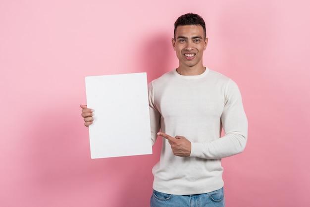 Mulâtre joyeux avec une feuille de papier à la main et pointant vers elle. - place pour le texte