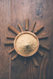 Mulethi ayurvédique ou bâton de racine de réglisse ou poudre de jeshthamadh servi dans un bol sur fond de mauvaise humeur
