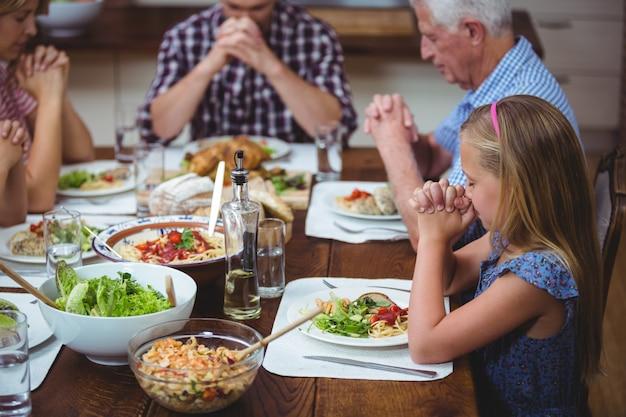 Multi génération famille prier avec grand-père assis à la table à manger