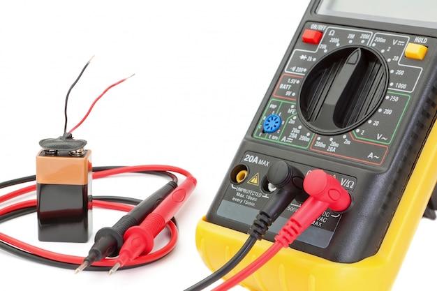 Multimètre électrique pour vérifier la résistance. sur un mur blanc avec batterie.