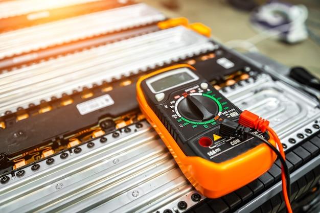 Le multimètre repose sur la batterie d'une voiture électrique