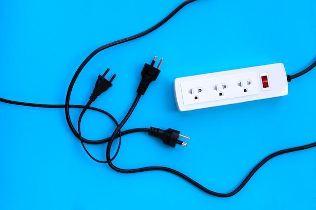 Multiprise électrique et fiche sur mur bleu. vue de dessus