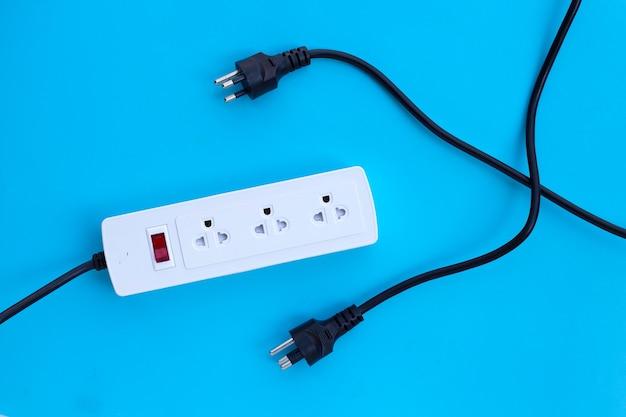 Multiprise électrique et fiches sur mur bleu. vue de dessus