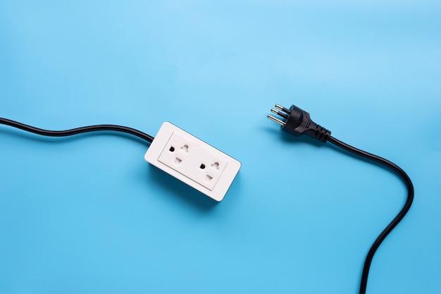 Multiprise électrique et prise sur fond bleu.