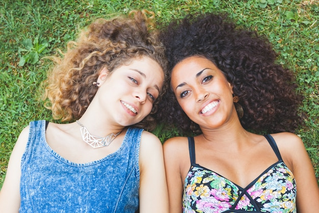 Multiracial, femme, couple, amis, coucher herbe