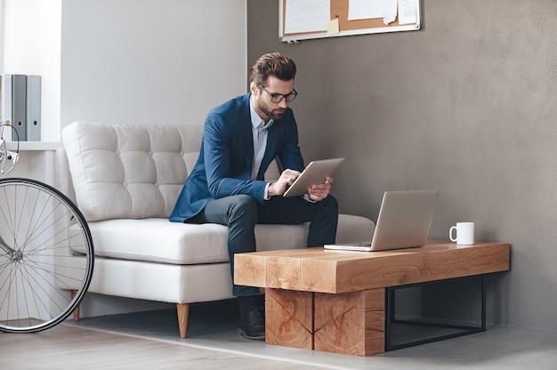 Multitâche. beau jeune homme portant des lunettes et travaillant avec touchpad assis sur le canapé au bureau