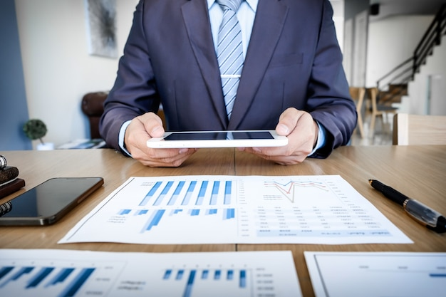 Multitâche. beau jeune homme travaillant avec le pavé tactile tout en étant assis sur le divan dans le bureau et le graphique statistique financier.