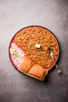 Mumbai style pav bhaji est un plat de restauration rapide de l'inde, se compose d'un curry de légumes épais servi avec un petit pain moelleux, servi dans une assiette