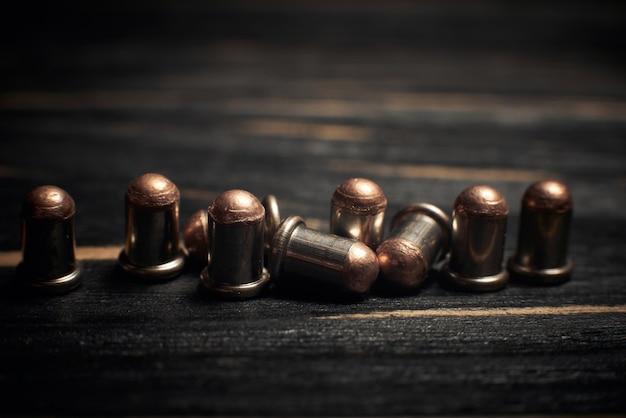 Munitions flobert 4mm gros plan sur fond sombre en bois foncé