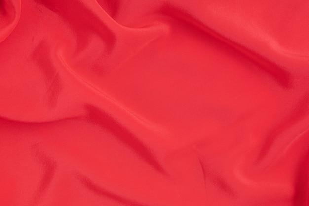 Mur abstrait de tissu de soie rouge. texture, luxe, mode, idée de style