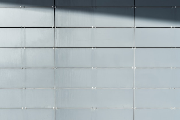 Mur de bâtiment moderne recouvert de panneaux de parement avec ombre. contexte architectural abstrait