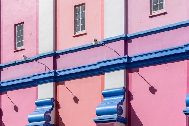 Mur d'un bâtiment peint en bleu, rose et violet sous la lumière du soleil