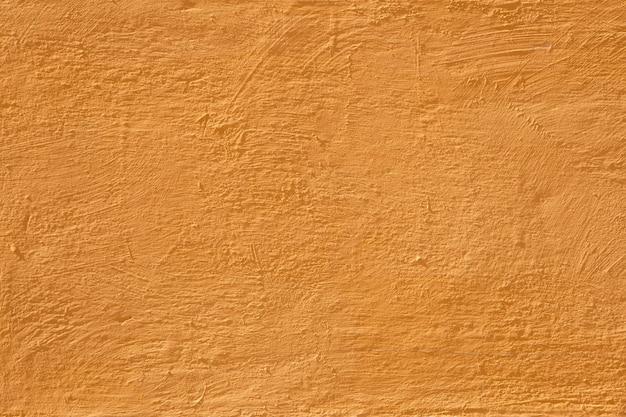 Mur de béton coloré, style vintage jaune chaud et lumineux de peinture de fond en ciment avec de petits détails de texture. ancienne surface de texture