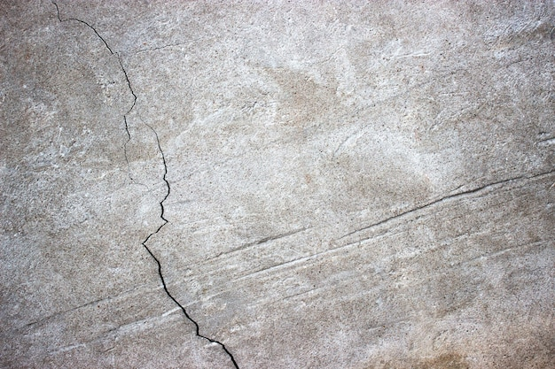 Mur de béton fissuré recouvert de surface de ciment gris comme arrière-plan