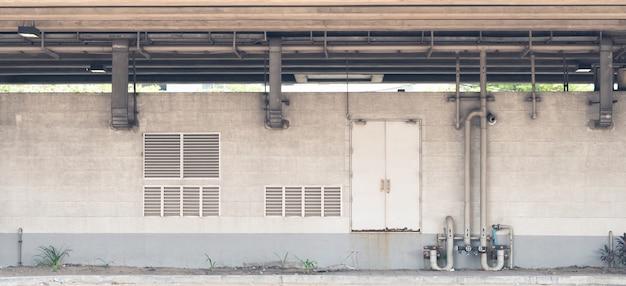 Mur de béton industriel gris vide avec un tuyau métallique. rideau de porte et volet, vintage gru