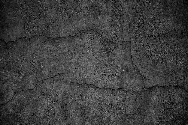 Mur de béton sombre avec des fissures. dalle noire détruite