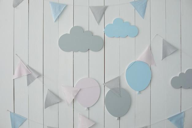 Le mur blanc est décoré de guirlandes de drapeaux et de montgolfières