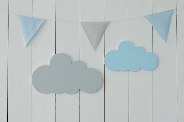 Le mur blanc est décoré de guirlandes de drapeaux et de nuages décoratifs décor pour les vacances chambre d'enfants élégante avec drapeaux suspendus décoration pour chambre de bébé