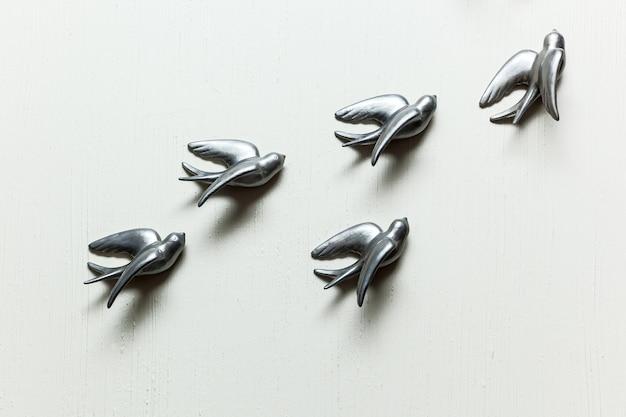 Mur blanc avec des oiseaux décoratifs en métal. décoration hirondelles au mur