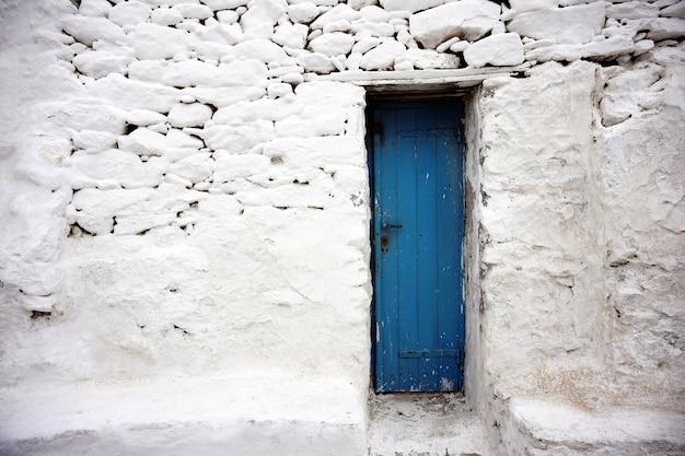 Mur blanc et petite porte bleue en grèce