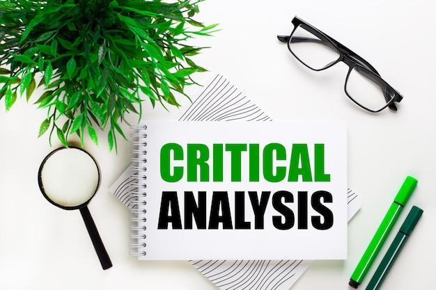 Sur un mur blanc se trouve un cahier avec le mot analyse critique, des lunettes, une loupe, des marqueurs verts et une plante verte