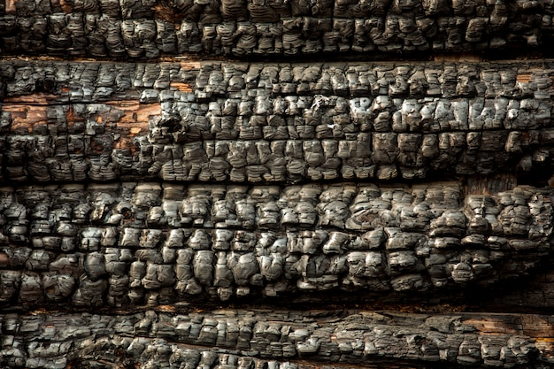 Mur en bois carbonisé noir carbonisé. texture rugueuse. conséquences après l'incendie. fragment de la maison incendiée