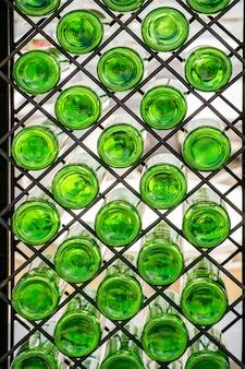 Mur avec des bouteilles en verre vert sur l'étagère. décoration d'intérieur