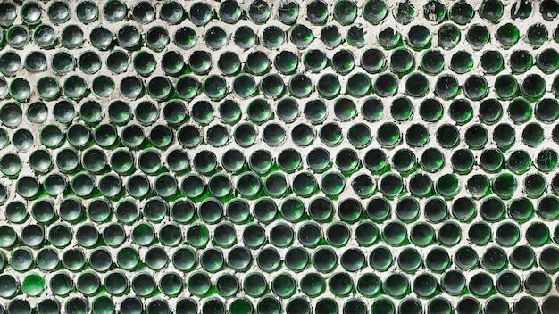 Un mur de bouteilles de vin vert. clôture à texture solide par le bas