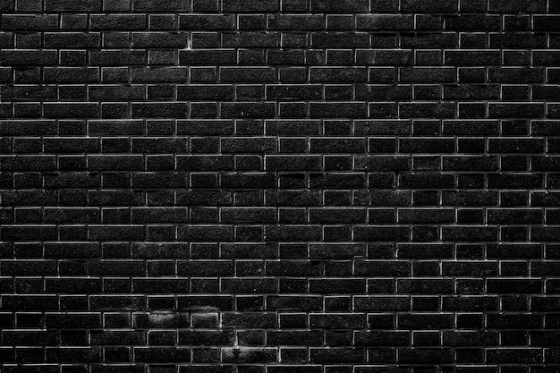 Le mur de brique noir foncé a une surface rugueuse comme image de fond.
